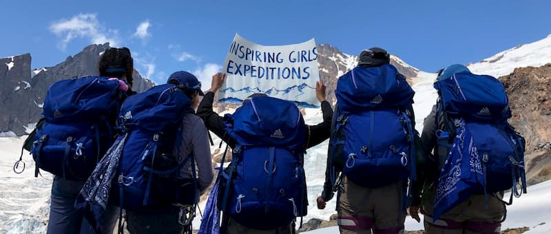 Photo of girls in the field holding sign